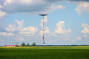 Drone flying over an Ohio soybean field with stinger platform suspended beneath.